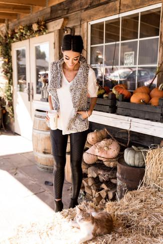 La versatilidad de un chaleco de pelo con relieve gris y unos pantalones pitillo de cuero negros los hace prendas en las que vale la pena invertir. Botines de cuero negros añaden la elegancia necesaria ya que, de otra forma, es un look simple.