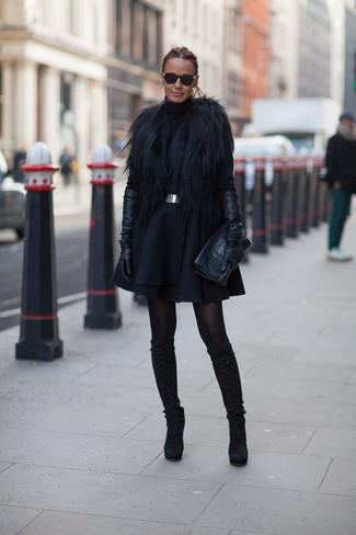 Cómo combinar: chaleco de pelo negro, jersey de cuello alto negro, falda skater de lana negra, botas de caña alta de ante negras