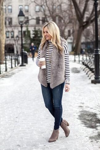 Cómo combinar: chaleco de pelo gris, jersey de cuello alto de rayas horizontales en blanco y negro, vaqueros pitillo azul marino, botines de ante grises