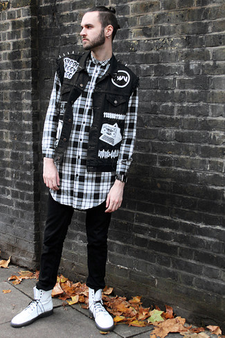 Cómo combinar: chaleco vaquero negro, camisa de manga larga de tartán en negro y blanco, vaqueros pitillo negros, botas casual de cuero blancas