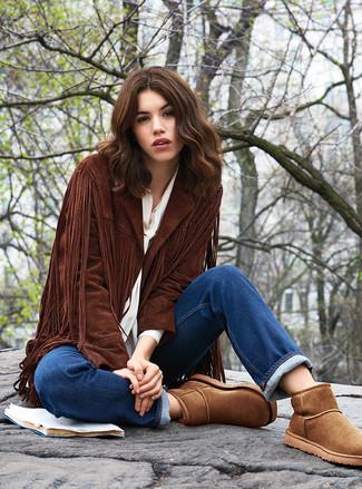 Cómo combinar: chaqueta abierta de ante сon flecos en marrón oscuro, blusa de botones blanca, vaqueros azules, botas ugg marrónes