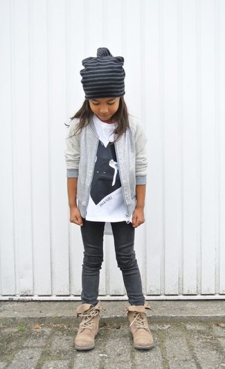 Cómo combinar: chaqueta plateada, camiseta estampada en blanco y negro, leggings en gris oscuro, botas marrón claro
