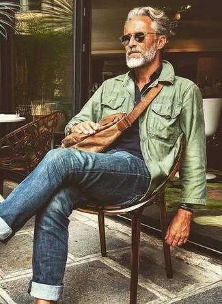 Cómo combinar: chaqueta campo verde oliva, camisa de manga larga azul marino, vaqueros azules, bolso mensajero de cuero marrón