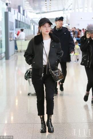 Para seguir las tendencias usa una chaqueta de piel de oveja negra y una gorra inglesa negra de mujeres de Puma. Un par de botines de cuero negros se integra perfectamente con diversos looks.