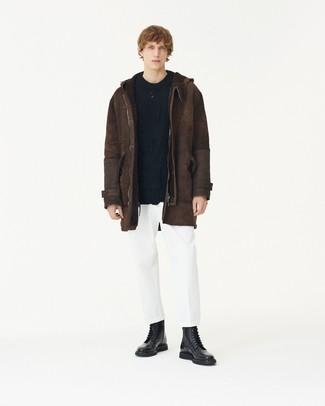 Cómo combinar: chaqueta de piel de oveja en marrón oscuro, jersey de ochos negro, pantalón chino blanco, botas casual de cuero negras