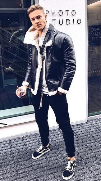 Cómo combinar: chaqueta de piel de oveja en negro y blanco, sudadera estampada gris, pantalón de chándal negro, tenis de lona en negro y blanco
