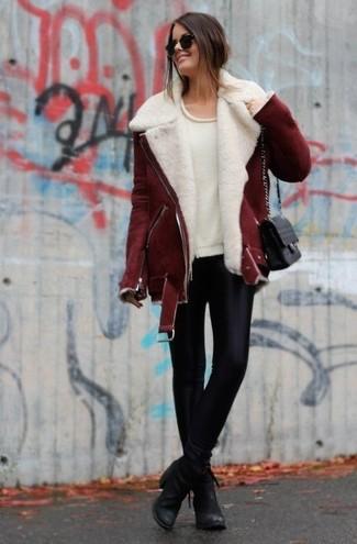 Una chaqueta de piel de oveja burdeos y unos leggings de cuero negros son una gran fórmula de vestimenta para tener en tu clóset. Dale onda a tu ropa con botines de cuero negros.