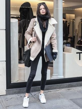 Cómo combinar: chaqueta de piel de oveja en beige, jersey con cuello circular negro, vaqueros pitillo negros, tenis de cuero blancos