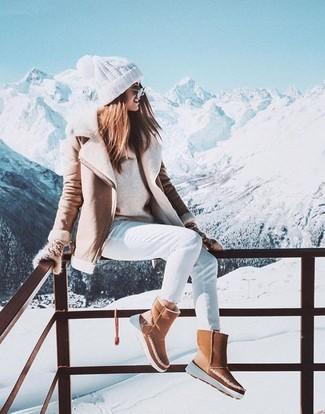 Cómo combinar: chaqueta de piel de oveja en beige, jersey con cuello circular en beige, vaqueros pitillo blancos, botas ugg marrón claro