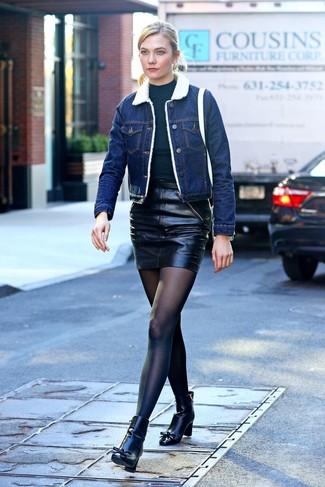 Cómo combinar: chaqueta de piel de oveja vaquera azul, jersey de cuello alto negro, minifalda de cuero negra, botines de cuero negros