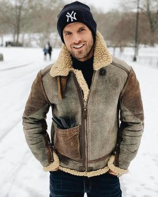 Cómo combinar: chaqueta de piel de oveja marrón, jersey de cuello alto negro, vaqueros azul marino, gorro estampado en negro y blanco