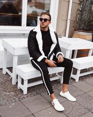 Cómo combinar: chaqueta de piel de oveja en negro y blanco, jersey de ochos negro, vaqueros pitillo en negro y blanco, tenis de cuero blancos