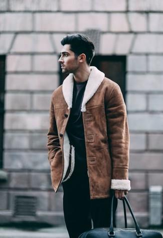 Cómo combinar: chaqueta de piel de oveja marrón, sudadera negra, pantalón de vestir negro, bolsa de viaje de cuero negra