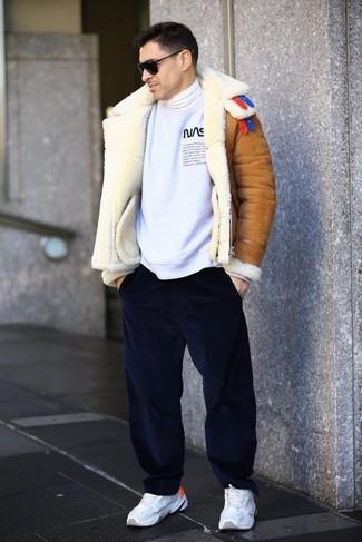 Cómo combinar: chaqueta de piel de oveja en tabaco, sudadera estampada en blanco y negro, jersey de cuello alto blanco, pantalón chino de pana azul marino