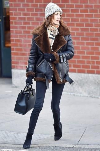Cómo combinar: chaqueta de piel de oveja negra, vaqueros pitillo negros, botines chelsea de ante negros, bolsa tote de cuero negra