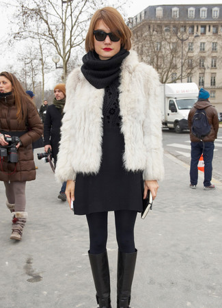 Cómo combinar: chaqueta de piel blanca, jersey con cuello circular con print de flores negro, minifalda de lana negra, botas de caña alta de cuero negras