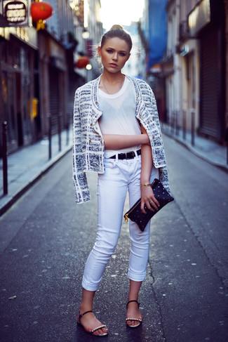Cómo combinar: chaqueta de tweed blanca, camiseta con cuello circular blanca, vaqueros pitillo blancos, sandalias planas de cuero con adornos negras