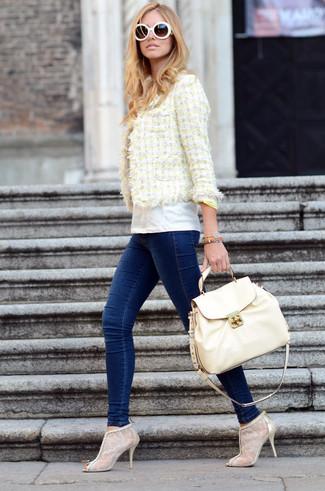 Cómo combinar: chaqueta de tweed amarilla, camiseta con cuello circular blanca, vaqueros pitillo azul marino, botines de encaje en beige