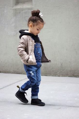 Cómo combinar: chaqueta acolchada en beige, sudadera con capucha negra, peto vaquero azul, botas negras