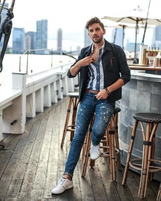 Cómo combinar: chaqueta estilo camisa azul marino, camisa de manga corta de rayas verticales en azul marino y blanco, vaqueros estampados azules, tenis blancos
