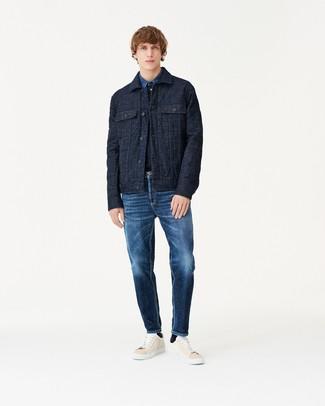 Cómo combinar: chaqueta estilo camisa acolchada azul marino, camisa vaquera azul, vaqueros azul marino, tenis de cuero en beige
