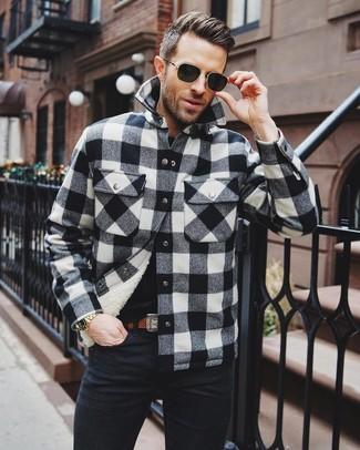 Cómo combinar: chaqueta estilo camisa a cuadros en negro y blanco, camiseta con cuello circular negra, vaqueros negros, correa de cuero marrón