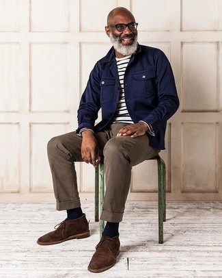 Perfecciona el look casual elegante en una chaqueta estilo camisa azul marino y un pantalón chino marrón. Este atuendo se complementa perfectamente con botas safari de ante en marrón oscuro.