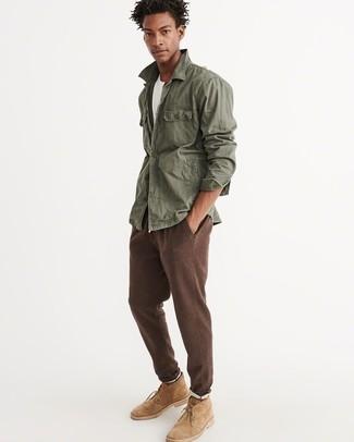 Cómo combinar: chaqueta militar verde oliva, camiseta con cuello circular blanca, pantalón de chándal marrón, botas safari de ante marrón claro