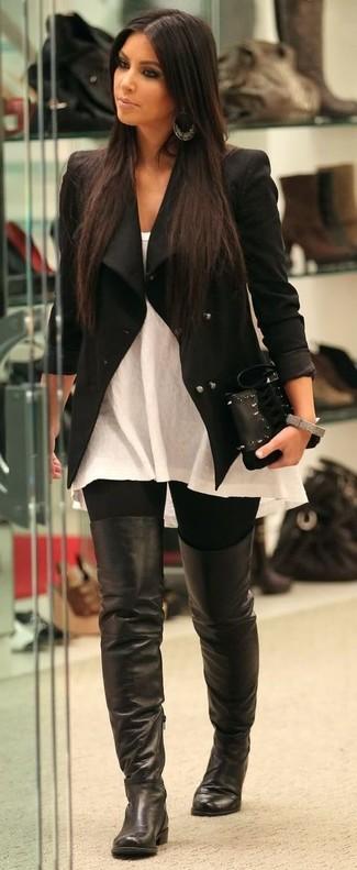 Cómo combinar: chaqueta motera negra, blusa sin mangas blanca, leggings negros, botas sobre la rodilla de cuero negras