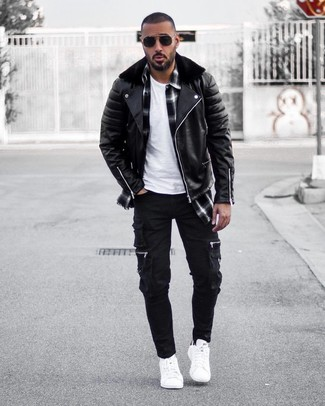 Cómo combinar: chaqueta motera de cuero negra, camisa de manga larga de tartán en negro y blanco, camiseta con cuello circular blanca, pantalón cargo negro
