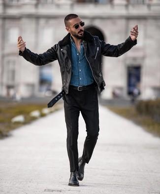 Cómo combinar: chaqueta motera de cuero negra, camisa vaquera azul, pantalón chino negro, botines chelsea de cuero negros