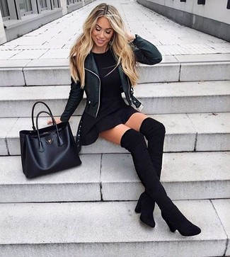 Cómo combinar: chaqueta motera de cuero negra, camiseta con cuello circular negra, falda skater negra, botas sobre la rodilla de ante negras