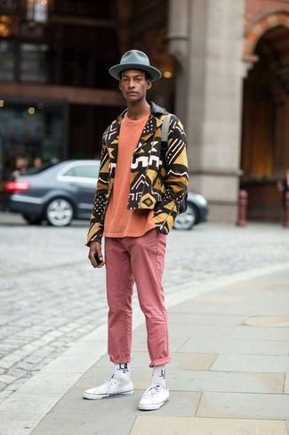 Cómo combinar: chaqueta motera estampada marrón, camiseta con cuello circular naranja, pantalón chino rosado, tenis de lona blancos