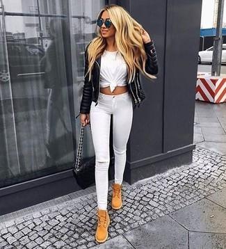Cómo combinar: chaqueta motera de cuero acolchada negra, camiseta con cuello circular blanca, vaqueros pitillo desgastados blancos, botas planas con cordones de ante marrón claro