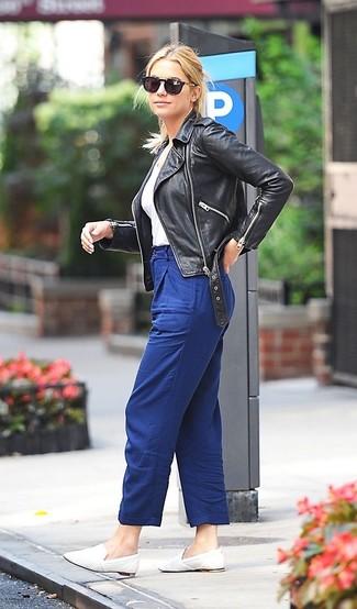 Cómo combinar: chaqueta motera de cuero negra, camiseta con cuello en v blanca, pantalón de pinzas azul, mocasín de cuero blancos
