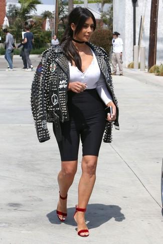 Cómo combinar: chaqueta motera de cuero con tachuelas negra, camiseta henley blanca, mallas ciclistas negras, sandalias de tacón de terciopelo rojas