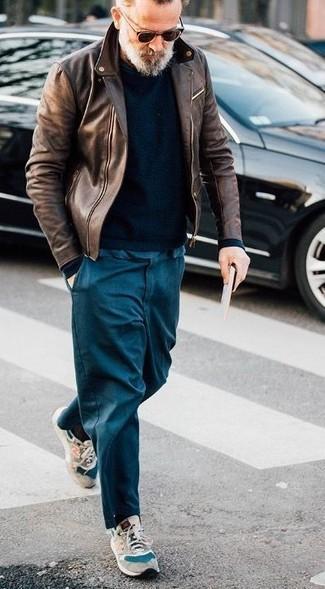 Cómo combinar: chaqueta motera de cuero marrón, jersey con cuello circular negro, pantalón chino azul marino, deportivas de ante en beige