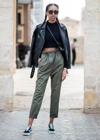 Cómo combinar: chaqueta motera de cuero negra, jersey corto negro, pantalones de pijama verde oliva, tenis de lona negros
