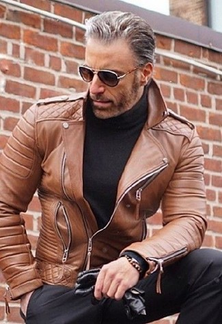 Cómo combinar: chaqueta motera de cuero marrón, jersey de cuello alto negro, pantalón de vestir negro, guantes de cuero negros