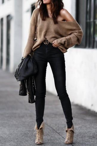 Cómo combinar: chaqueta motera de cuero negra, jersey oversized marrón, vaqueros pitillo negros, botines con cordones de ante en beige