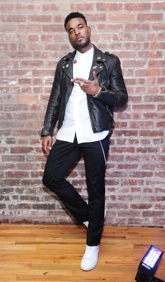 Cómo combinar: chaqueta motera de cuero negra, camisa de vestir blanca, pantalón chino negro, tenis de cuero blancos