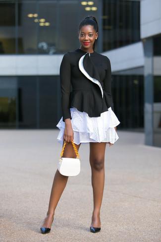 Cómo combinar: chaqueta motera negra, falda skater con ojete blanca, zapatos de tacón de cuero negros, bolso bandolera de cuero blanco
