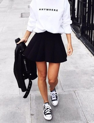 Cómo combinar: chaqueta motera de cuero negra, jersey con cuello circular estampado en blanco y negro, falda skater negra, tenis de lona en negro y blanco