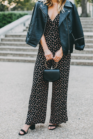 Cómo combinar: chaqueta motera de cuero negra, mono con print de flores negro, sandalias de tacón de ante negras, cartera sobre de cuero negra