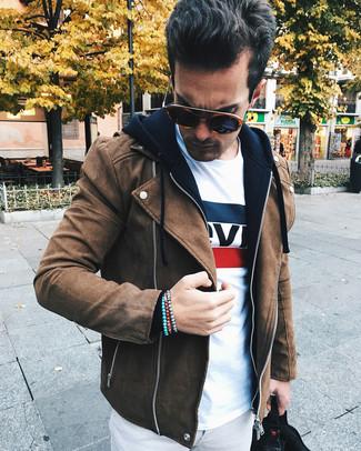 Cómo combinar: chaqueta motera de ante marrón, sudadera con capucha negra, camiseta con cuello circular estampada blanca, pantalón chino gris