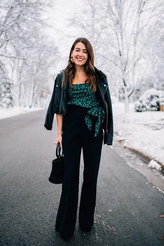 Cómo combinar: chaqueta motera de cuero negra, top con hombros descubiertos estampado verde oscuro, pantalones anchos negros, zapatos de tacón de ante negros