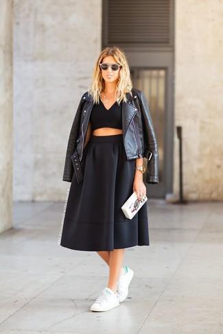 Una chaqueta motera de cuero negra y una falda midi plisada negra son prendas que debes tener en tu armario. Haz este look más informal con tenis en blanco y verde.