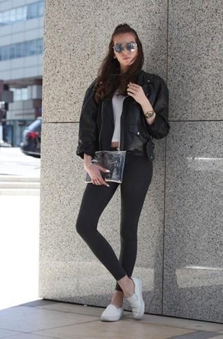 Cómo combinar: chaqueta motera de cuero negra, top corto blanco, leggings en gris oscuro, zapatillas slip-on de lona blancas