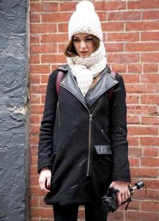 Cómo combinar: chaqueta motera de lana negra, vaqueros pitillo negros, mochila de cuero burdeos, gorro de punto blanco