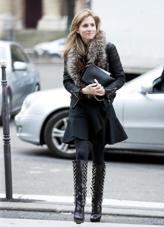Cómo combinar: chaqueta motera de cuero acolchada negra, vestido de vuelo con volante negro, botas de caña alta de cuero negras, cartera sobre de cuero negra
